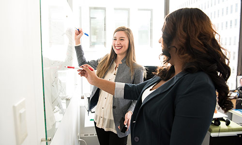 Two Women Collaborating on a Whiteboard About Hr Values
